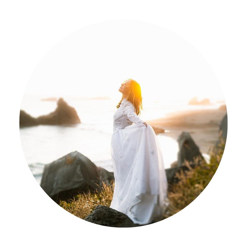 Frau im weißen Kleid steht am Strand und atmet. Sie hat die Arme ausgebreitet.